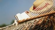 Woman lying on hammock, reading book, rear view